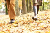 落ち葉の道を歩く男女の足元