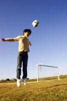サッカーボールでヘディングする男の子