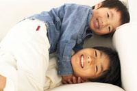 ソファの上でじゃれる兄弟 02336001261A| 写真素材・ストックフォト・画像・イラスト素材|アマナイメージズ