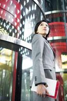 手帳を持ってビルの前に立つ女性