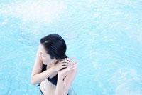 プールで髪をしぼる女性