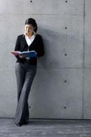 コンクリートの壁の前でファイルを見る女性
