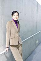 コンクリートの壁の前に立つ女性