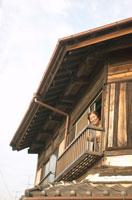 二階から顔を出す60代の女性 02336001482| 写真素材・ストックフォト・画像・イラスト素材|アマナイメージズ