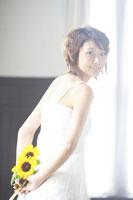 向日葵を持つ女性