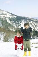 雪山にいる兄妹と雪ダルマ