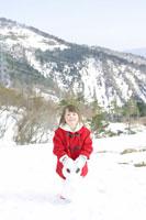 雪山にいる女の子と雪ダルマ