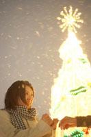 クリスマスツリーの前にいる女性
