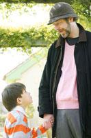公園を散歩するお父さんと男の子