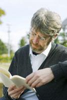 ベンチで本を読む外国人男性