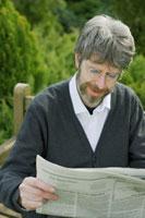 ベンチで新聞を読む外国人男性