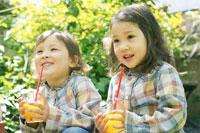庭でジュースを飲む双子の女の子 02336002071| 写真素材・ストックフォト・画像・イラスト素材|アマナイメージズ