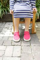 庭で椅子に座った女の子の足もと 02336002077  写真素材・ストックフォト・画像・イラスト素材 アマナイメージズ