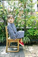 庭で椅子に座った女の子
