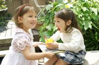 庭でジュースを飲む双子の女の子