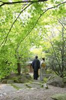日本庭園を歩く着物姿のシニア夫妻