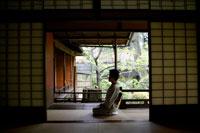 回廊に座る着物姿のシニア女性