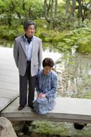 日本庭園の橋の上に立つシニア夫婦 02336002138| 写真素材・ストックフォト・画像・イラスト素材|アマナイメージズ