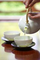 急須でお茶を注ぐシニア女性の手元