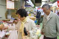 市場で買い物をするシニア夫婦