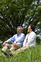 野原に腰掛けるシニア夫婦 02336002323| 写真素材・ストックフォト・画像・イラスト素材|アマナイメージズ