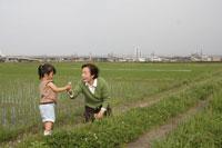 畦道で花を摘むおばあちゃんと孫