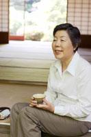 縁側でお茶を飲むシニア女性 02336002359| 写真素材・ストックフォト・画像・イラスト素材|アマナイメージズ