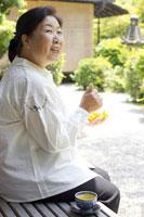 縁側でみかんを食べるシニア女性 02336002362B| 写真素材・ストックフォト・画像・イラスト素材|アマナイメージズ