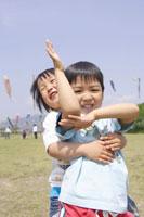 草原で遊ぶ男の子2人 02336002417| 写真素材・ストックフォト・画像・イラスト素材|アマナイメージズ