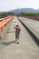 橋を渡る男の子2人の後ろ姿