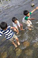 川で水遊びをする男の子3人