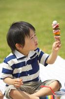 草原でお弁当をたべる男の子