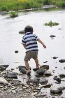 川で水遊びをする男の子の後ろ姿