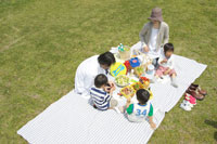 のはらでお弁当を食べる家族