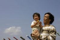 鯉のぼりと父親に抱かれる男の子
