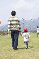 草原を歩く父と男の子の後ろ姿