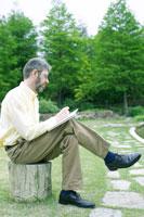 公園でスケッチをする外国人男性