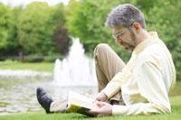 公園で読書をする外国人男性