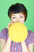 黄色い風船を膨らます女性