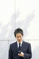 携帯メールを打つビジネスマン