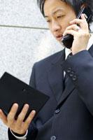 手帳を見ながら電話をかける男性