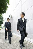 壁の前を歩くビジネスマン二人