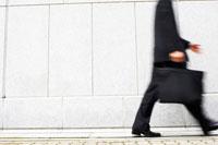 壁の前を歩くビジネスマン