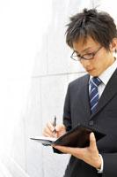 手帳にメモをするビジネスマン