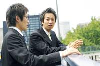 歩道橋で話すビジネスマン二人