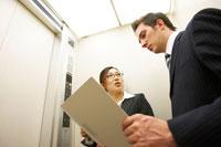 エレベーターで話をするスーツ姿の男女