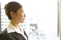 窓の外を見つめるビジネスウーマン