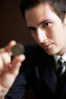コインを見つめるビジネスマン 02336002810| 写真素材・ストックフォト・画像・イラスト素材|アマナイメージズ