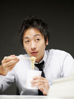 カップラーメンを食べるビジネスマン