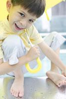黄色い傘をさす裸足の男の子
